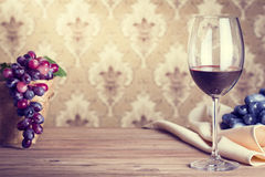 Glass of red wine. Glass of wine on wooden table against of vintage wallpaper background Stock Image