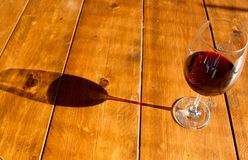 Glass of red wine and its shadow on the wooden table royalty free stock images