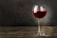 Glass of red wine on a wooden table Stock Photography