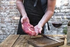 A glass of red wine on a wooden table. A man in a black leather apron prepares beef meat for dinner and a party. Copy space stock image