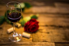 Glass of red wine on a wooden table with red rose stock photos