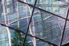 Glass reflection. Close up of multi-coloroed reflections on a glass structure. A Tree can be seen Royalty Free Stock Photography