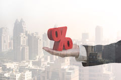 Glass reflection of hand showing 3D red percentage sign. With city buildings background Stock Photos