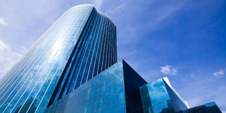 Glass reflective office building. Against blue sky with clouds and sun light Stock Photos