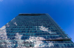 Glass reflective office buildings against blue sky with clouds and sun light Royalty Free Stock Image