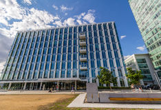 Glass reflective office buildings against blue sky with clouds and sun light Royalty Free Stock Photography