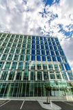 Glass reflective office buildings against blue sky with clouds and sun light Royalty Free Stock Photos