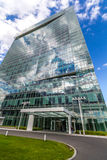 Glass reflective office buildings against blue sky with clouds and sun light Stock Images