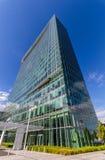 Glass reflekterande kontorsbyggnader mot blå himmel med moln och solen tänder Arkivbilder