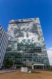 Glass reflekterande kontorsbyggnader mot blå himmel med moln och solen tänder Arkivfoto
