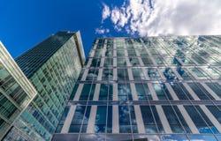 Glass reflekterande kontorsbyggnader mot blå himmel med moln och solen tänder Royaltyfri Foto