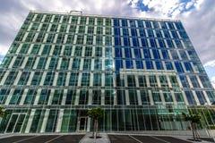 Glass reflekterande kontorsbyggnader mot blå himmel med moln och solen tänder Arkivbild