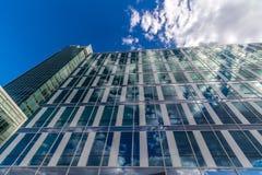 Glass reflekterande kontorsbyggnader mot blå himmel med moln och solen tänder Royaltyfri Fotografi