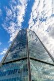 Glass reflekterande kontorsbyggnader mot blå himmel med moln och solen tänder Arkivfoton