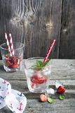 Glass of refreshing ice water with slices  juicy ripe strawberries, mint leaves and  cubes in a simple wooden background Stock Photos
