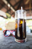 Glass of refreshing iced soda. Standing on a counter top with a pair of red sunglasses with shallow depth of field Stock Photos