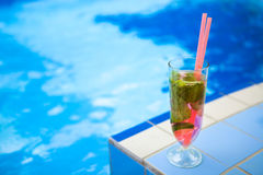 Glass of refreshment drink with strawberry mojito on a pool side Royalty Free Stock Images