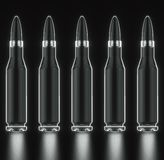 Glass Rifle Bullet Line on Black. Tiling pattern of glass rifle bullets against a black background and arranged on a rough reflective black surface. This image Stock Photography