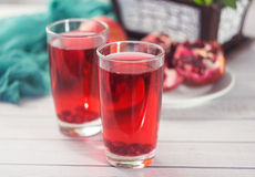 A glass of ripe pomegranate juice on wooden background. Healthy living concept Stock Images