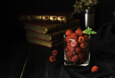 Glass with ripe raspberries and mint on the background of books , selective focus, concept Royalty Free Stock Image