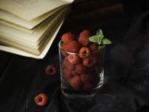Glass with ripe raspberries and mint on the background of books , selective focus, concept. A glass with ripe raspberries and mint on the background of books on Stock Photo