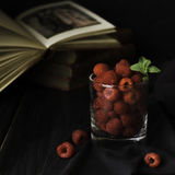 Glass with ripe raspberries and mint on the background of books , selective focus, concept. A glass with ripe raspberries and mint on the background of books on Royalty Free Stock Photo