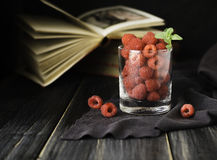 Glass with ripe raspberries and mint on the background of books , selective focus, concept. A glass with ripe raspberries and mint on the background of books on Stock Photography