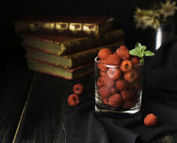 Glass with ripe raspberries and mint on the background of books , selective focus, concept. A glass with ripe raspberries and mint on the background of books on Royalty Free Stock Photos