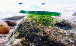 Glass on the rock. Shard of glass, grinded with water, lies on a stone Royalty Free Stock Images