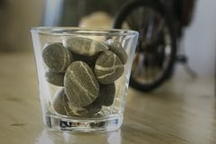 A glass of rocks/stones. An image aimed for home decor and styling. Contains: glass, grey rocks, miniature bicycle and a living room dresser Stock Images
