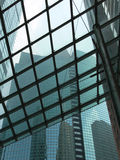 Glass roof. Look through the roof of an office building at a skyscraper royalty free stock photo