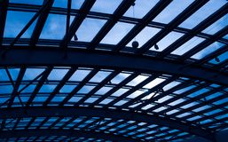 Glass Roof Against Blue Sky And Sunshine. Roof made by steel and glass against blue sky and sun shine. Part of construction industry Stock Photos