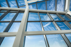 Glass roof and blue sky. Modern office building glass ceiling against blue skies Royalty Free Stock Image