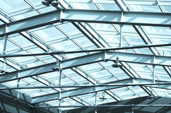 Glass roof in building, Under the roof. Glass and metal constructions of modern office building with outside blue sky. Royalty Free Stock Photography