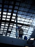 Glass roof of railway station. Indoors from below view of glass roof construction of railway station, two people in winter clothes standing on balcony Stock Photos