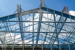Glass roof, steel structure. Glass roof in a steel structure against a blue sky with clouds Stock Image