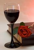 Glass and rose. Wineglass, rose and book in warm lighting stock photography