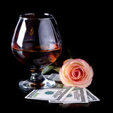 Glass, rose and dollars. Stock Photography