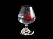 Glass with rose and pearl necklace Royalty Free Stock Photos