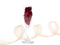Glass with rose petals and ribbon. Royalty Free Stock Image