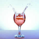 Glass of rose punch with two opposite splashes Royalty Free Stock Photo