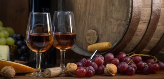 Glasses of rose wine cheeses grapesand barrel on brown wooden background. Glass of rose wine cheeses grapesand barrel on brown wooden background stock photo