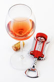Glass of rose wine and corkscrew Stock Photos