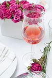 Glass of rose wine and festive dining table setting with pink ro. A glass of rose wine and festive dining table setting with pink roses, white tablecloths and Royalty Free Stock Images