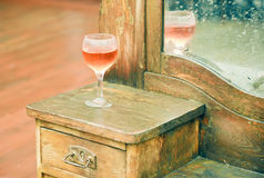Glass of rose wine left on an old dresser in a rural house. Glass of rose wine left on an old dresser with mirror and cracked texture. Still life in a rural Stock Photo