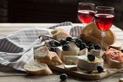 A glass of rose wine served with cheese plate blackberries and baguette. Assortment of cheese with berries on wooden background. A glass of rose wine served Stock Images