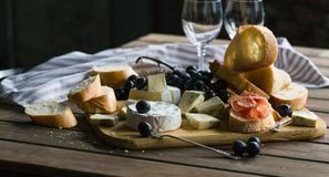 A glass of rose wine served with cheese plate blackberries and baguette. Assortment of cheese with berries on wooden background. A glass of rose wine served Royalty Free Stock Images