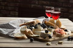 A glass of rose wine served with cheese plate blackberries and baguette. Assortment of cheese with berries on wooden background. A glass of rose wine served Royalty Free Stock Photography