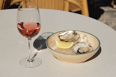 Glass of rose wine on the table in street cafe with oyster. Glass of rose wine with oyster on plate n on the table in street cafe setting Royalty Free Stock Photo