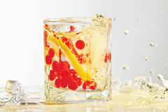 Glass of rum, ice, lemon and cranberry with splash Stock Images